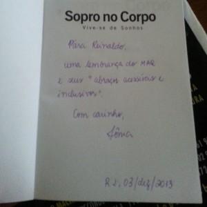"""Foto da página de rosto do livro """"Sopro no Corpo"""", com uma dedicatória a Reinaldo Ferraz feita pela esposa do MAQ"""