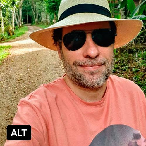 Selfie de Reinaldo Ferraz usando um chapeu tipo panamá de óculos escuros e de camisa rosa. Está em uma estrada de terra em meio a mata. No canto inferior esquerdo há um box preto com as letras ALT